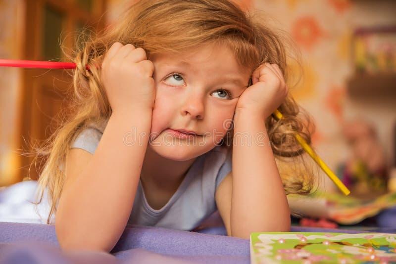 一个小金发女孩,被翻动的头发的面孔有可卷起的眼睛的 库存图片