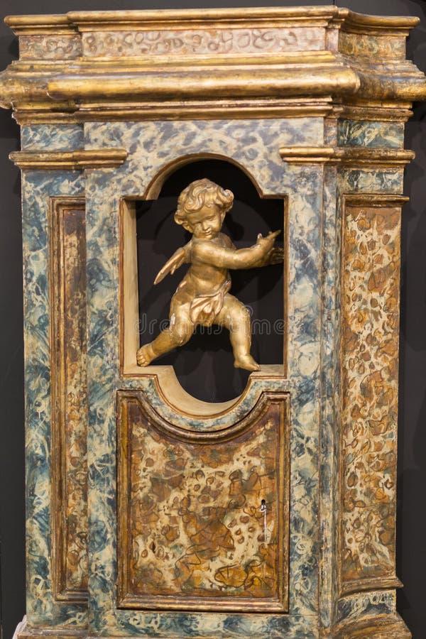 一个小金黄天使孩子的小雕象:古典雕塑 免版税库存照片