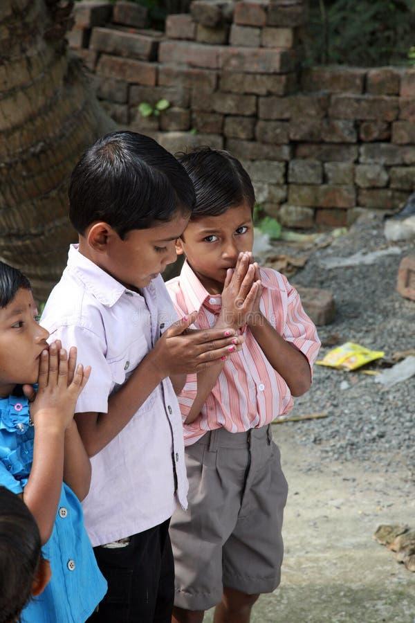 一个小组年轻孟加拉天主教徒在保佑的前祈祷圣母玛丽亚的雕象在Bosonti,印度 免版税库存照片