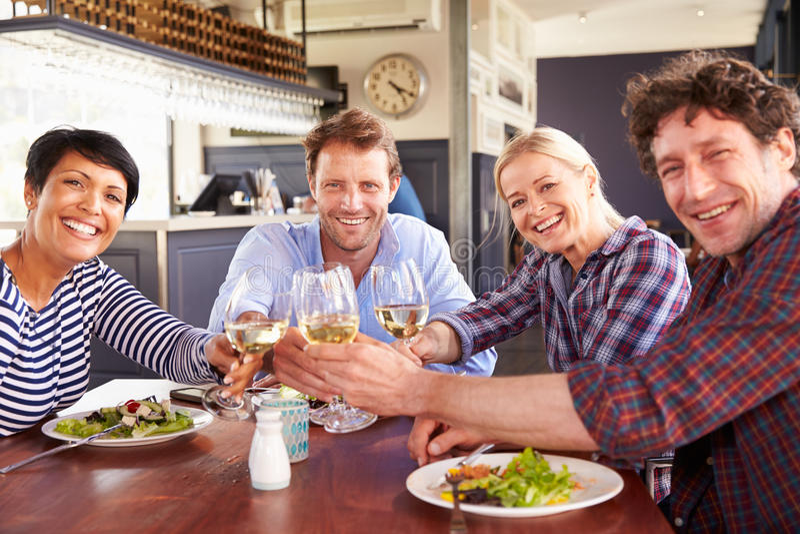 一个小组朋友吃午餐在餐馆 库存图片