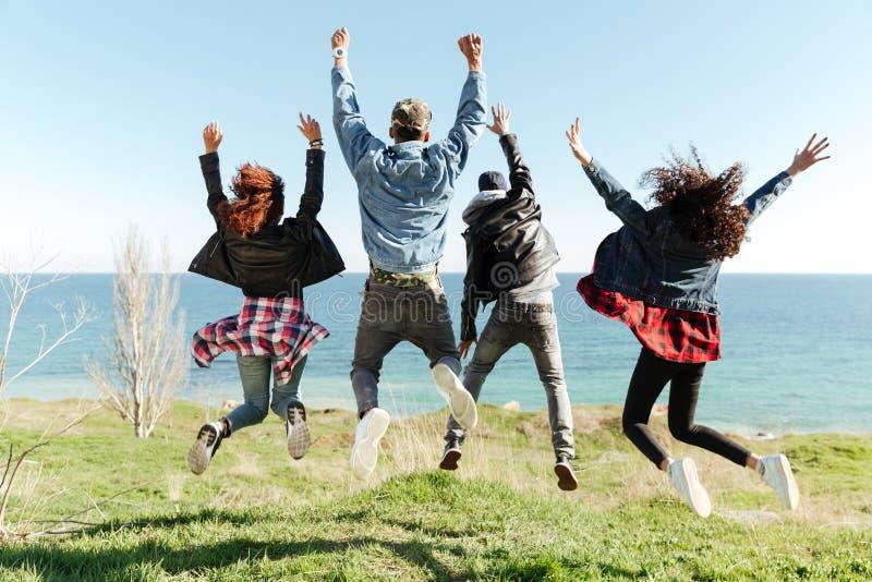 一个小组的后面看法图片朋友跳跃 免版税库存照片