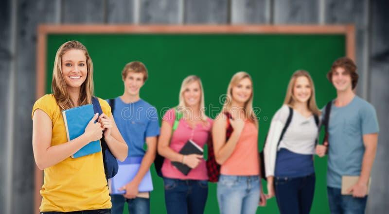 一个小组的综合图象并肩作战象一个女孩的大学生在他们前面站立 免版税图库摄影