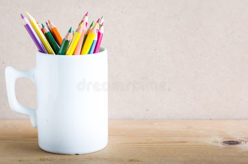 一个小组颜色在木头的一个白色杯子书写 免版税库存图片