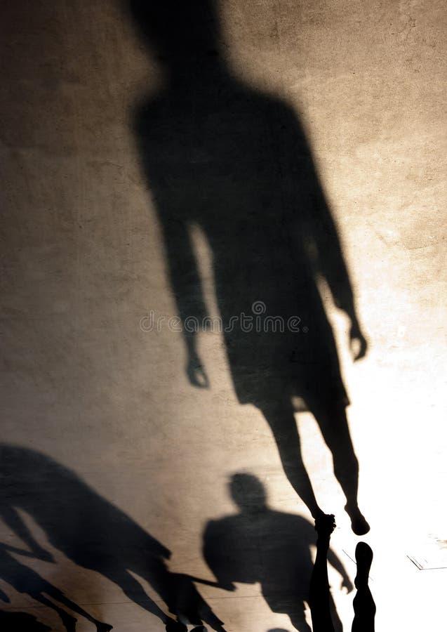 一个少妇和家庭的模糊的剪影阴影与chil 库存照片