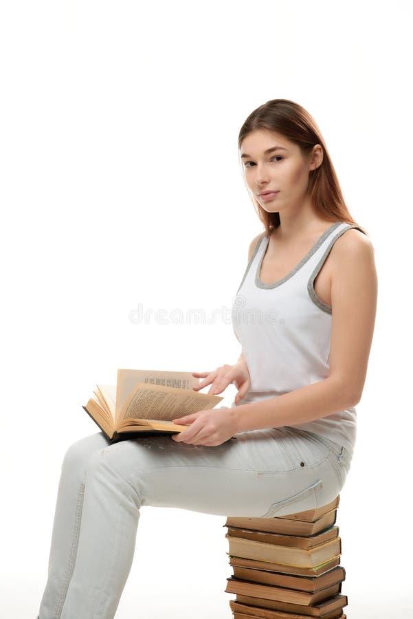 一个少妇坐堆书 保留在她的膝部的书 免版税库存照片