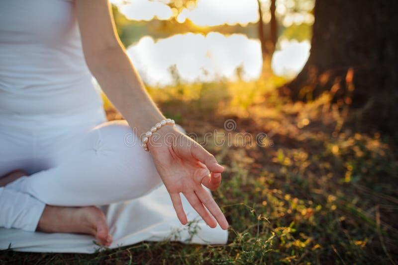 一个少妇的手被折叠用一个特别方式入瑜伽m 免版税库存图片