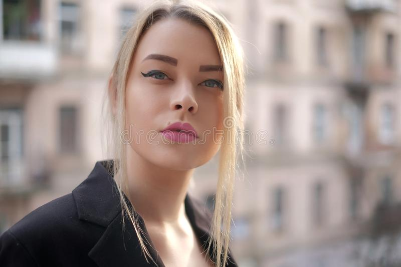一个少妇的画象一个黑衣服特写镜头的反对一个模糊的城市的背景落日的光芒的 免版税图库摄影