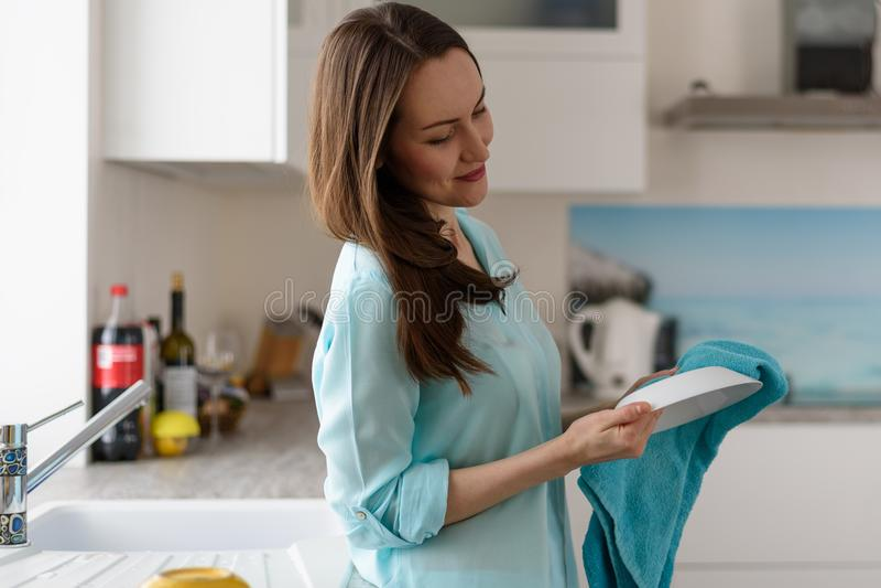 一个少妇的画象厨房内部抹的与一块干毛巾干净的盘,清洗房子 免版税库存照片