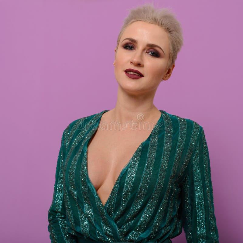 一个少妇的画象有短的理发的在与深刻的领口的一件绿色晚礼服在紫色背景 免版税库存照片