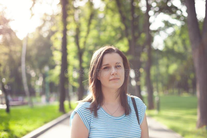 一个少妇的画象在公园由背后照明点燃了 库存图片