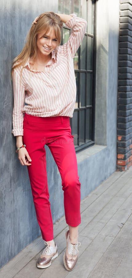 一个少妇的画象在女衬衫、红色丝光斜纹棉布裤子和金子方穿戴了 摆在灰色墙壁旁边 方式 免版税库存图片