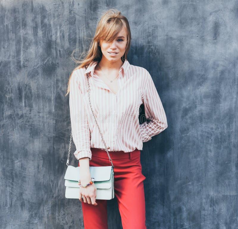 一个少妇的画象在女衬衫,红色丝光斜纹棉布裤子,在她的肩膀的一块提包绿松石穿戴了 摆在灰色墙壁旁边 库存图片