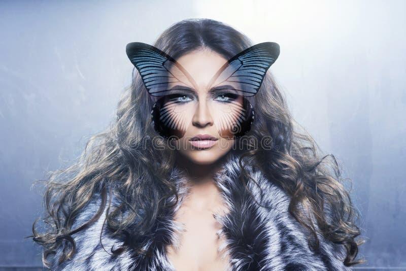 一个少妇的画象有一只蝴蝶的在她的面孔 免版税库存照片