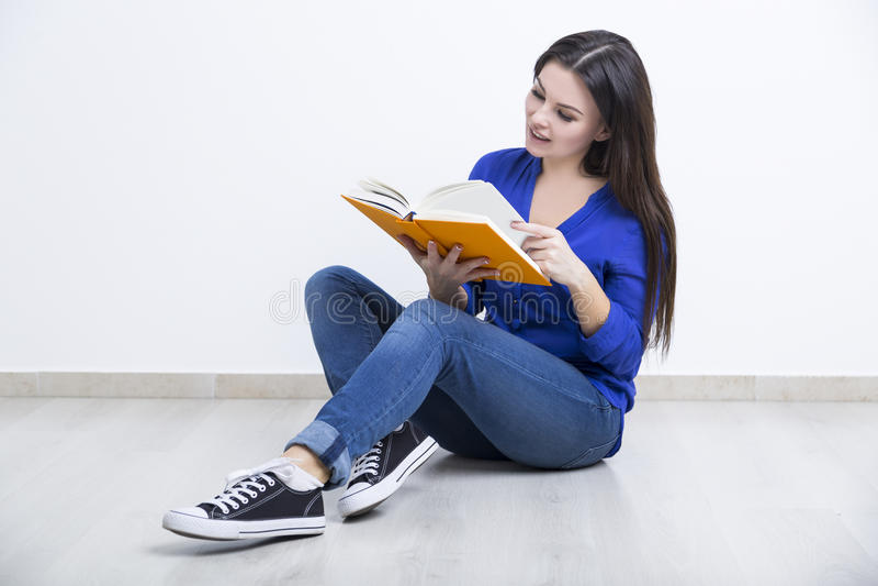 一个少妇的画象有橙色书的 免版税库存图片
