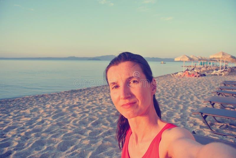 一个少妇的Selfie海滩的在日落;退色的,减速火箭的样式 免版税库存图片
