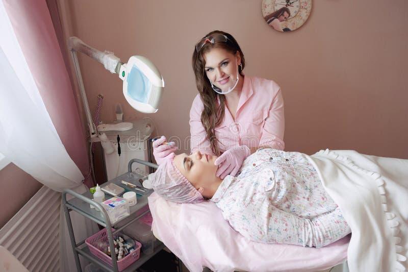 一个少妇说谎并且得到她的在美容院的眼眉构成  使用在眼眉的永久构成 大师w 库存照片