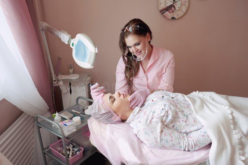 一个少妇说谎并且得到她的在美容院的眼眉构成  使用在眼眉的永久构成 大师w 库存图片