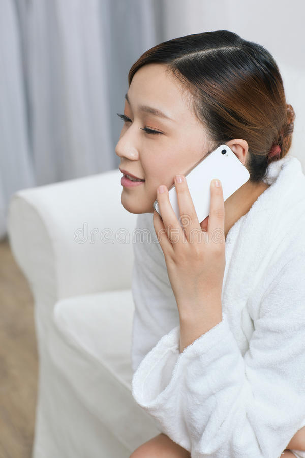 一个少妇谈话由在温泉沙龙的手机 库存图片