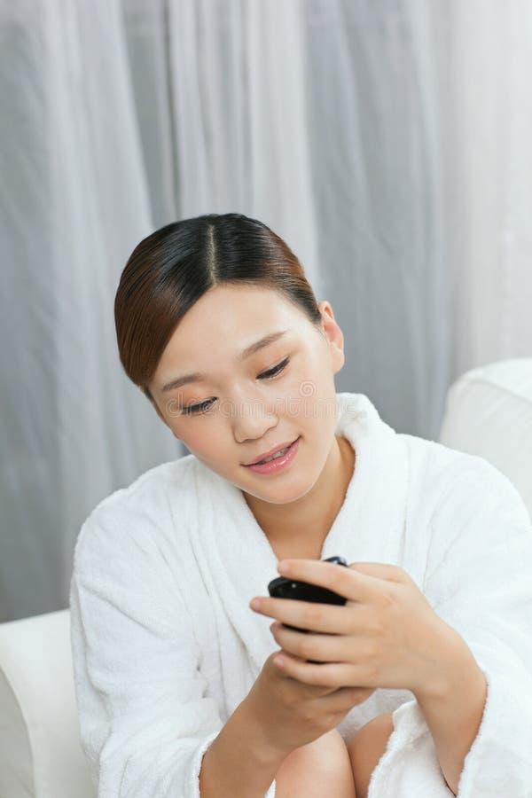 一个少妇谈话由在温泉沙龙的手机 库存照片