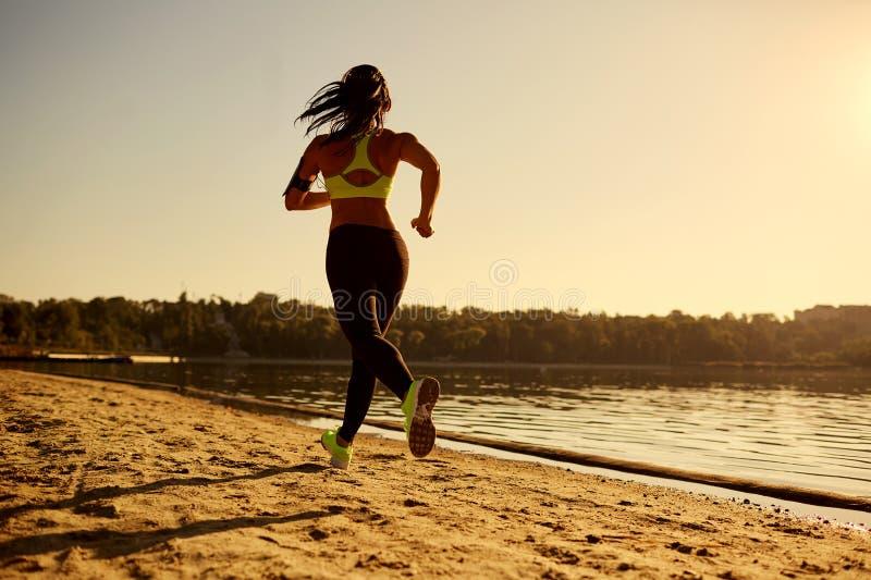 一个少妇赛跑者运行在日落在一个公园在湖 免版税库存图片