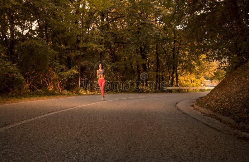 一个少妇,户外跑步的跑在柏油路,前面 库存图片