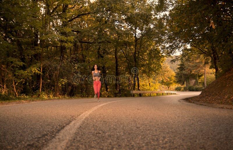 一个少妇,户外跑步的跑在柏油路,前面 图库摄影