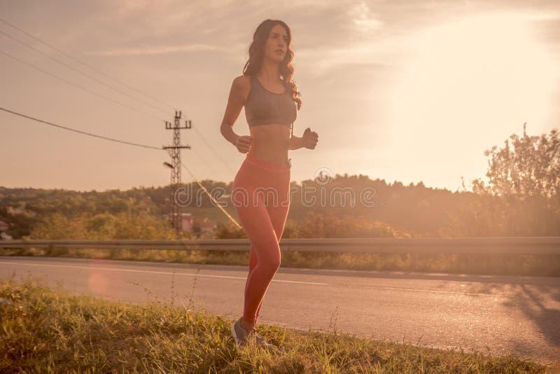 一个少妇,户外跑步,体育穿衣,晴朗太阳的天空, 免版税库存照片