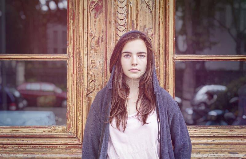 一个少年女孩的画象在一老woode前面的 库存照片