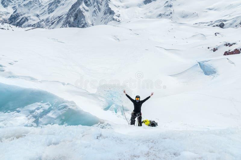 一个山指南和在冰川的骑马技能的准备在冰斧的在北高加索 手在胜利 免版税图库摄影