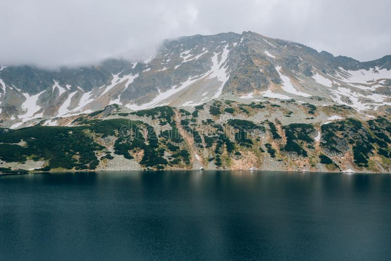 一个山湖在一阴天,五个湖塔特拉山脉国家公园,波兰Dolina Pieciu Stawow Polskich谷的看法  免版税库存照片