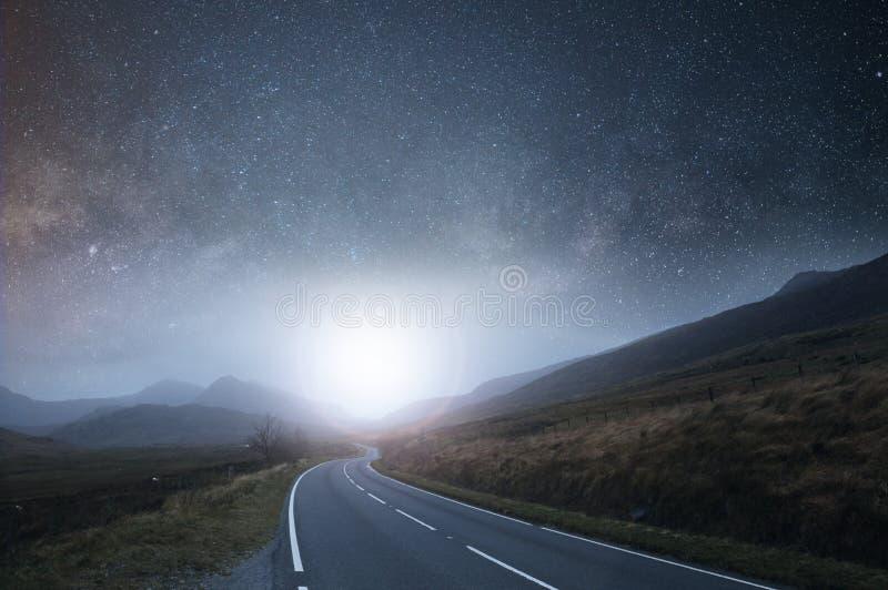 一个山路标题到距离里在与星的晚上在与发光在天际的明亮的光的天空 免版税图库摄影
