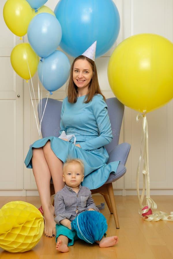 一个岁男婴第一个生日 有坐在椅子的母亲的小孩孩子 免版税库存图片