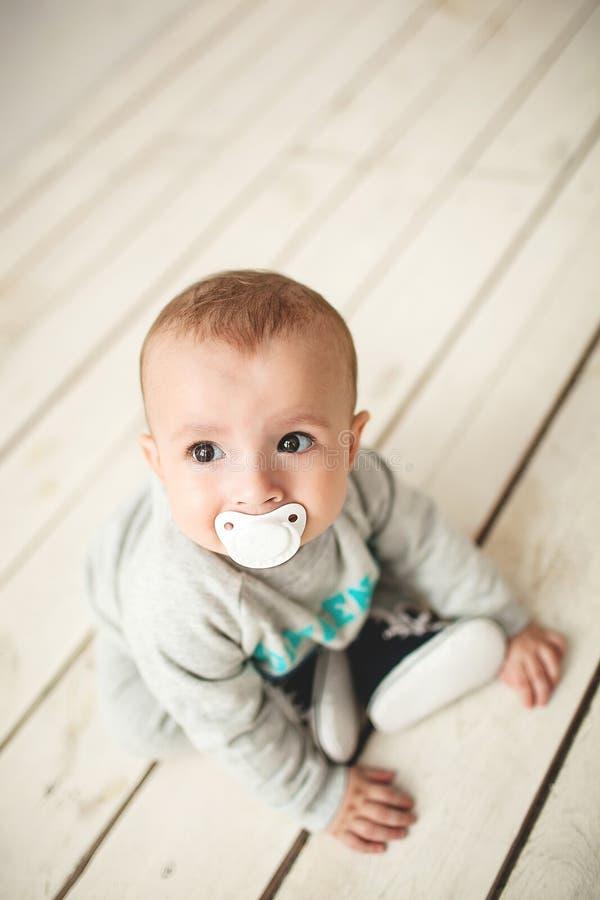 一个岁逗人喜爱的男婴坐木地板 图库摄影