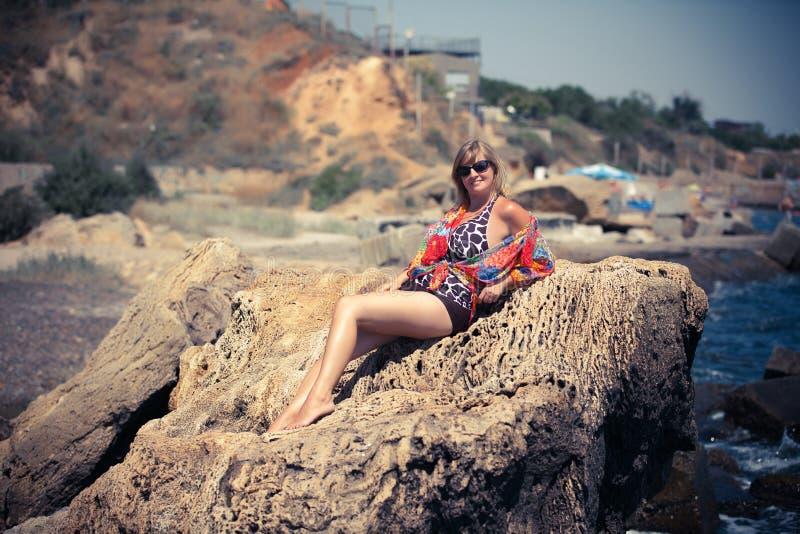 一个岩石的妇女由反对天空的海 库存图片
