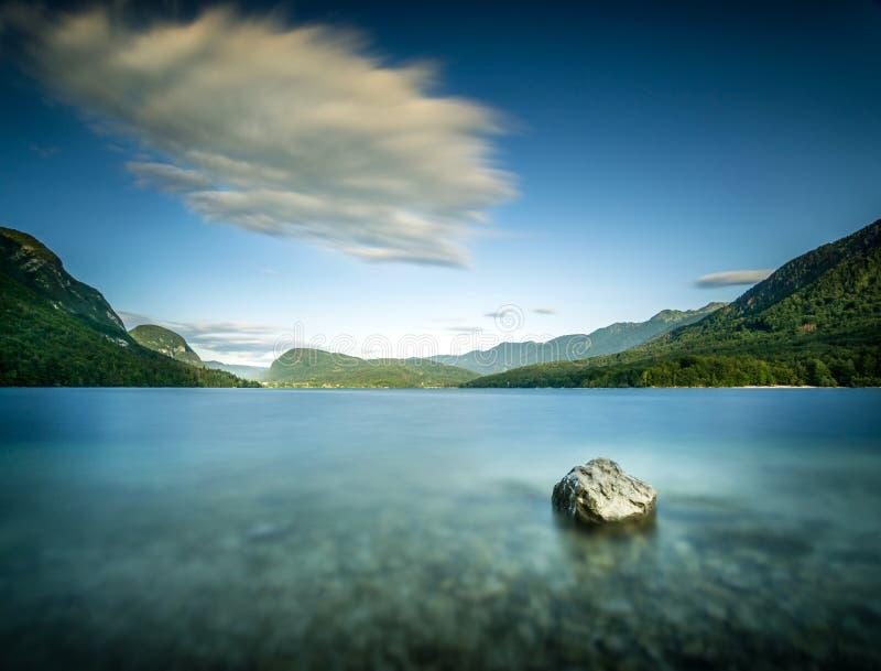 一个岩石的长的曝光在湖水中在Pebble海滩 免版税库存照片