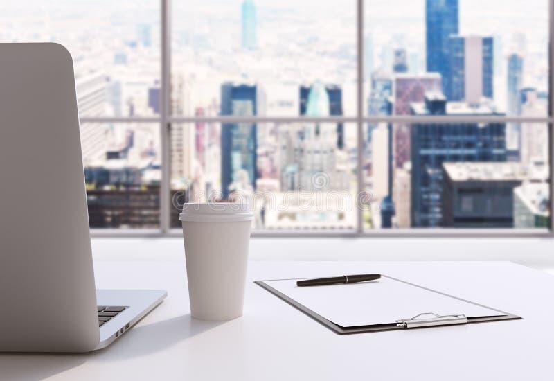 一个工作场所在一个现代全景办公室在曼哈顿,纽约 膝上型计算机、笔记薄和咖啡杯在白色桌上 3 皇族释放例证
