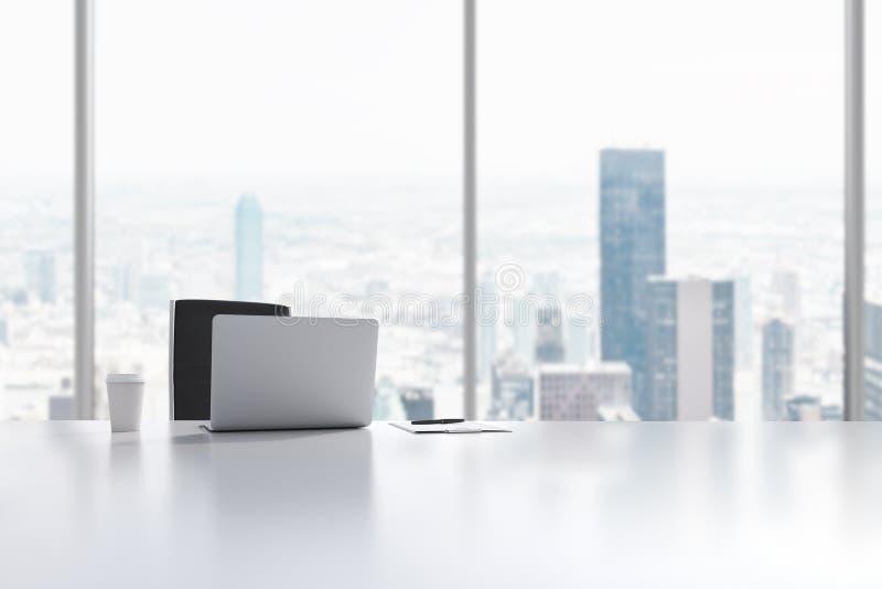 一个工作场所在一个现代全景办公室在曼哈顿,纽约 膝上型计算机、笔记薄和咖啡杯在白色桌上 免版税库存照片