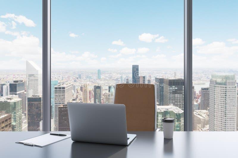 一个工作场所在一个现代全景办公室有纽约视图 一张灰色桌,棕色皮椅 库存照片