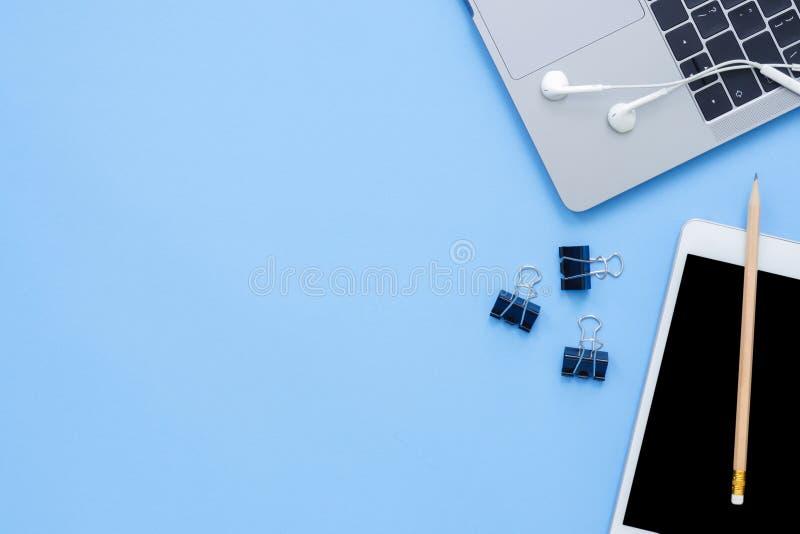 一个工作空间的平的位置顶视图大模型照片与膝上型计算机、耳机和嘲笑的在蓝色淡色背景的片剂 库存照片
