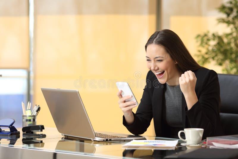 读一个巧妙的电话的激动的女实业家 免版税库存图片
