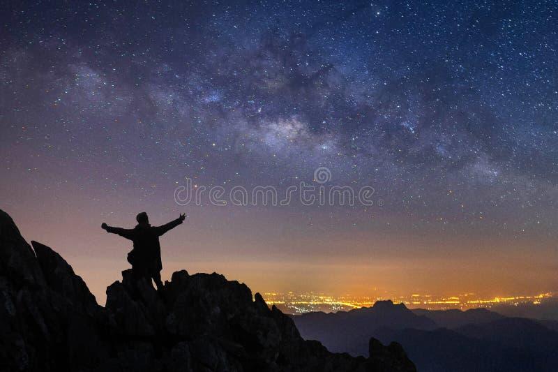 一个常设人的剪影在峭壁顶部的与胳膊被举在夜风景山和银河星系 库存照片