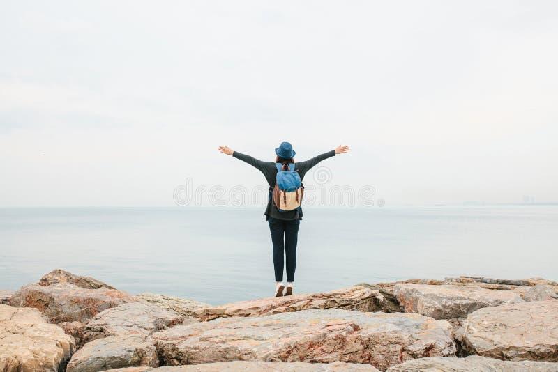 一个帽子的一个女孩旅客有在海旁边的一个背包的举她的手  旅行,休息,远足,自由 免版税图库摄影