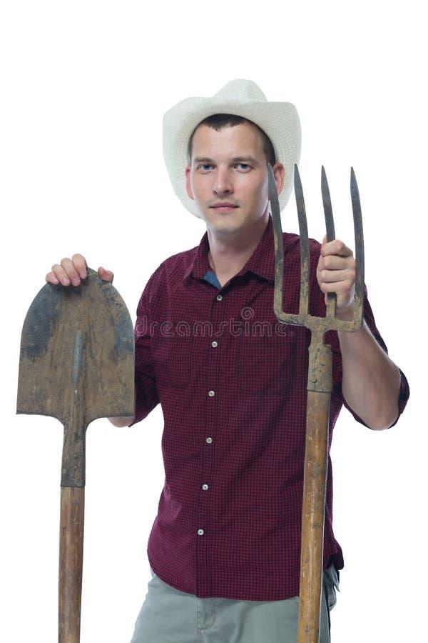 一个帽子的一位农夫有铁锹和干草叉的在手中 免版税库存照片