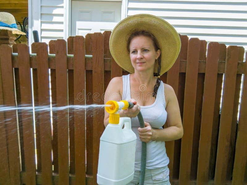 一个帽子的可爱的妇女使用压力喷雾器 库存图片