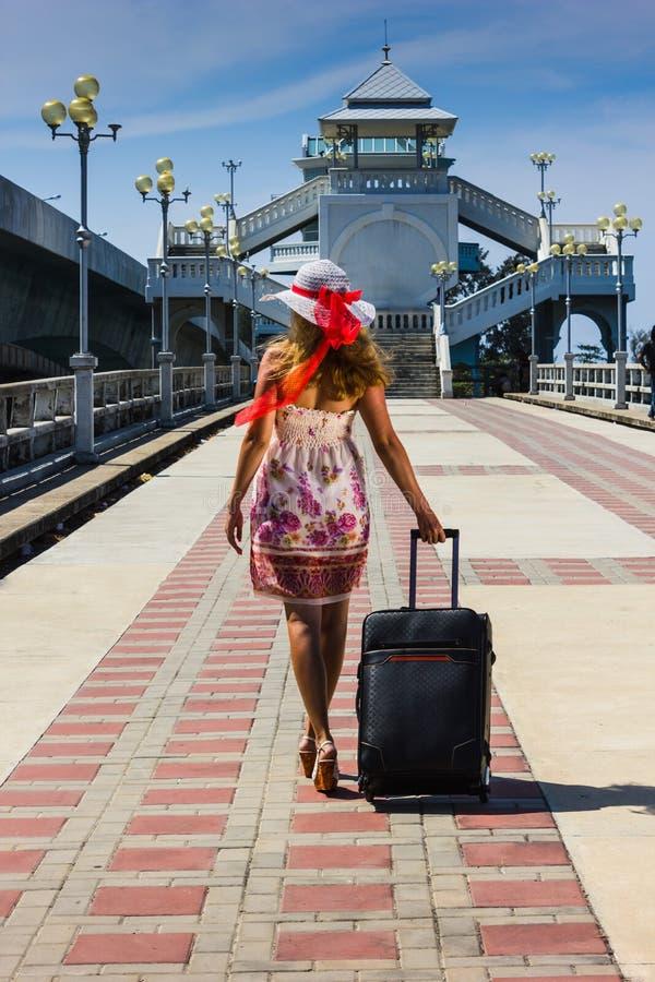 一个帽子的女孩带着去在休息的手提箱 免版税库存图片