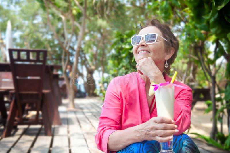 一个帽子的美丽的年长妇女有鸡尾酒的在手中 夏天 免版税库存图片
