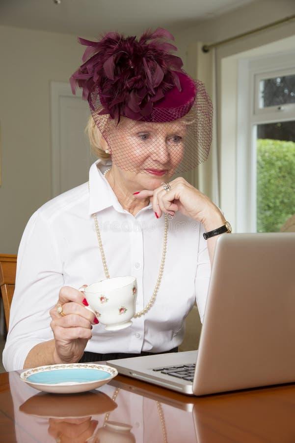 一个帽子的年长妇女使用便携式计算机 免版税库存图片