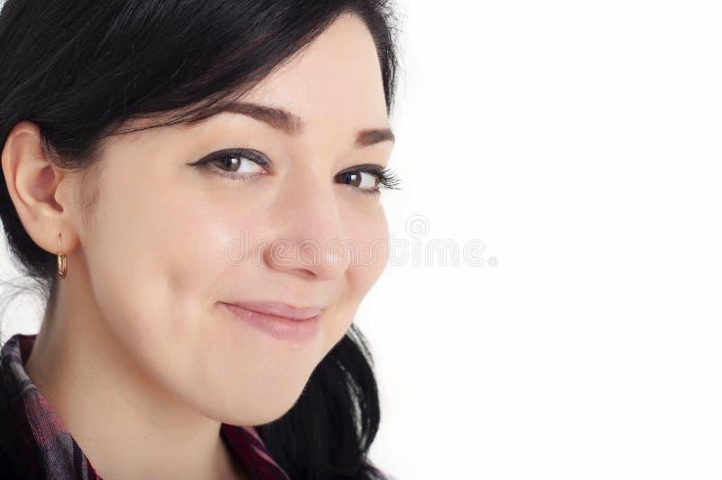 一个年轻、快乐的、美丽的褐发女孩,脸颊上带着可爱的酒窝,笑着看着镜头,脸上带着幸福 免版税图库摄影