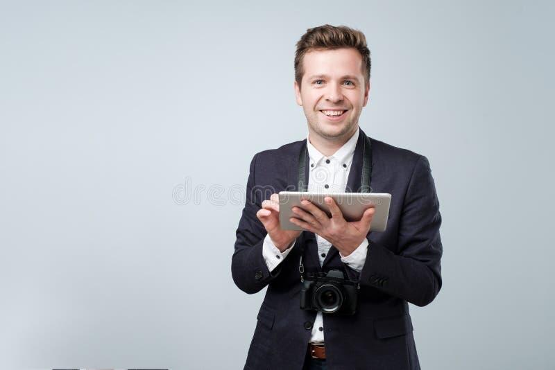 一个年轻人使用在灰色背景的片剂计算机和看照相机的画象衣服的 免版税库存图片
