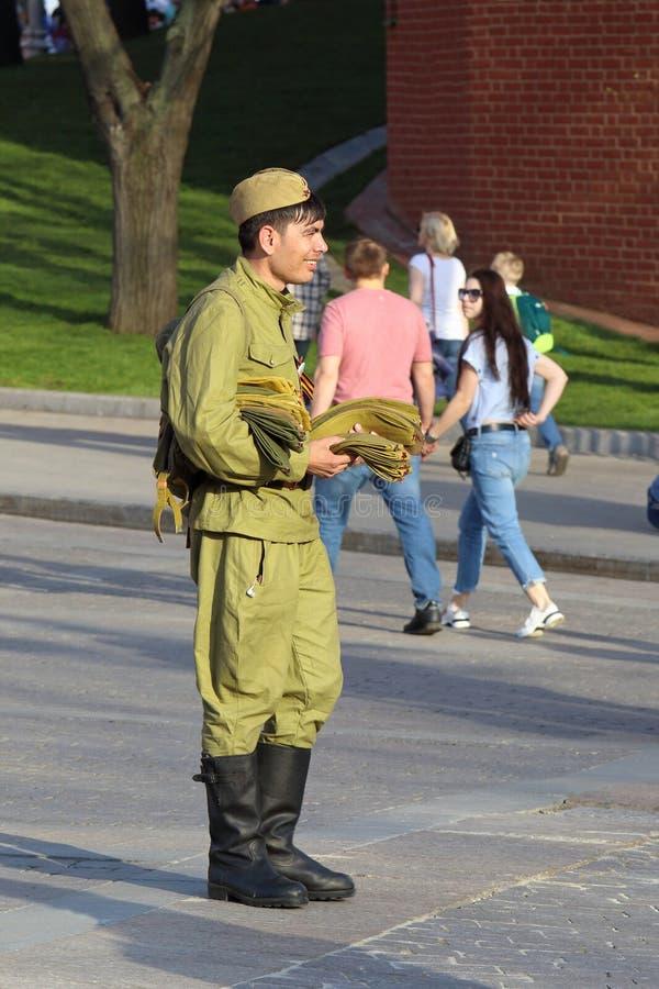 一个年轻人在克里姆林宫附近卖军事纪念品 图库摄影